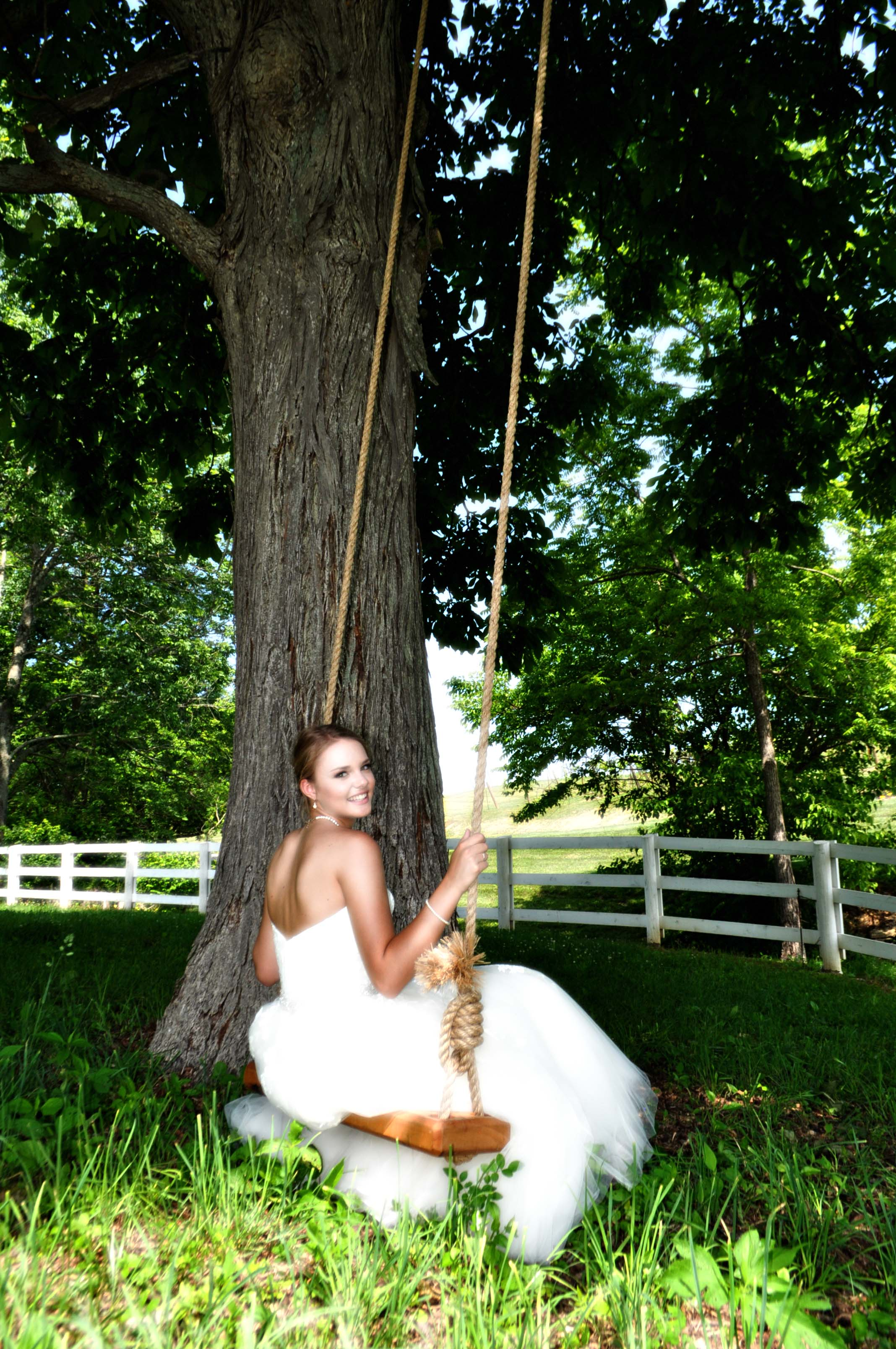 Bride on tree swing from behind
